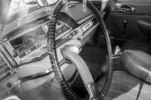 Černobílá fotografie detailu volantu auta